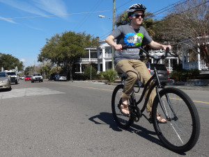 Aaron Holly, manager of the College's  Bike Share program, rides near Colonial Lake in downtown Charleston, S.C.