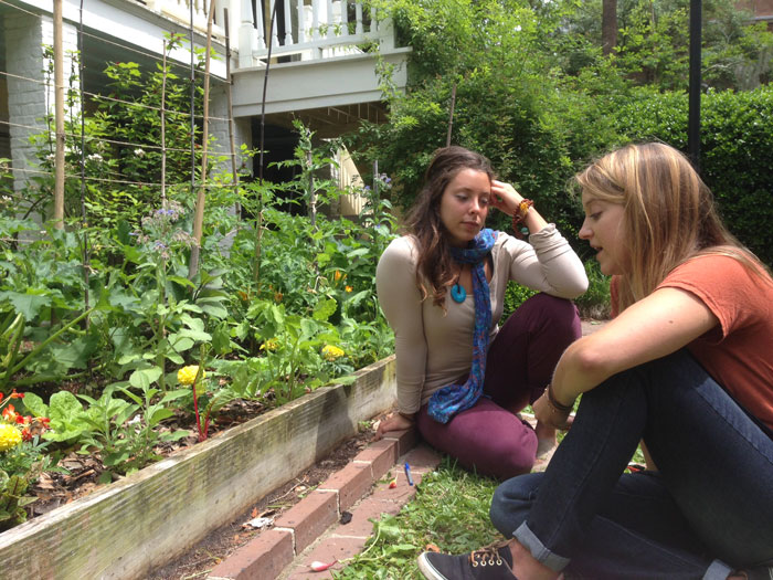 Lexa Keane '14 and Katie Erwin '15 chat beside one of their hidden campus gardens.