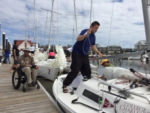 Anthony Radetic (seated), one of 17 wounded war veterans participating in the advanced racing camp, prepares to board one of the College's 22-foot sloops.