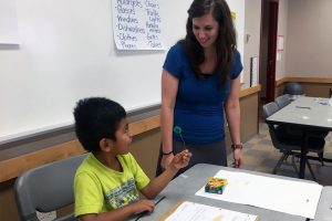 An Elementary Engineer camper talks with a teacher about his pollinator design.