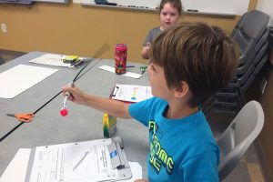 An Elementary Engineer camper demonstrates how the stem of his pollinator bounces with just a little movement.