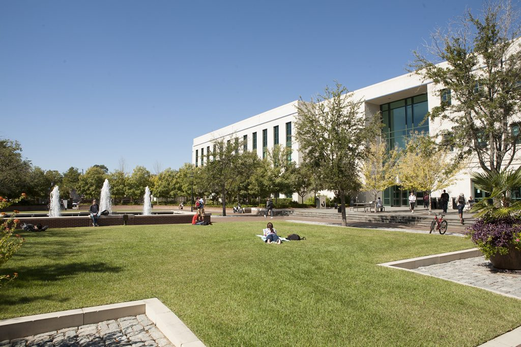 Students lounge on Rivers Green outside Addlestone Library.