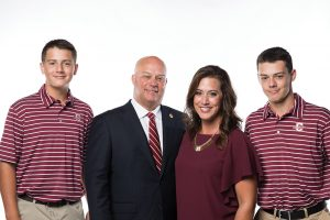 Coach Chad Holbrook (center) with his wife, Jenn, and sons Cooper (left) and Reece (right).