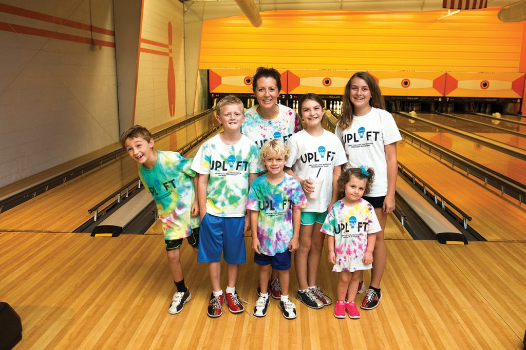 Anna Lonon, center, with children at an UPLIFT event last fall at The Alley.