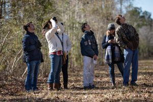 Biology professor Melissa Hughes with students at Stono Preserve for an ornithology class.