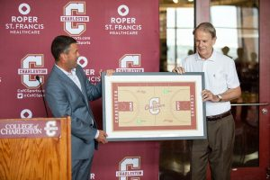 Director of Athletics Matt Roberts presents Kresse with a framed replica of the newly renamed Kresse Court at TD Arena.