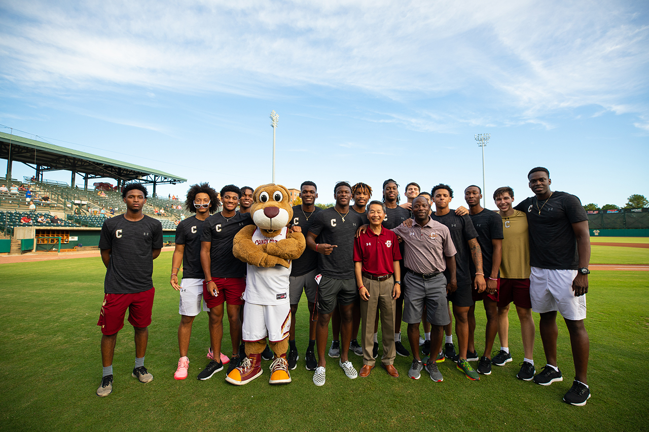 College of Charleston President Andrew T. Hsu with the men's basketball team at a Charleston RiverDogs game