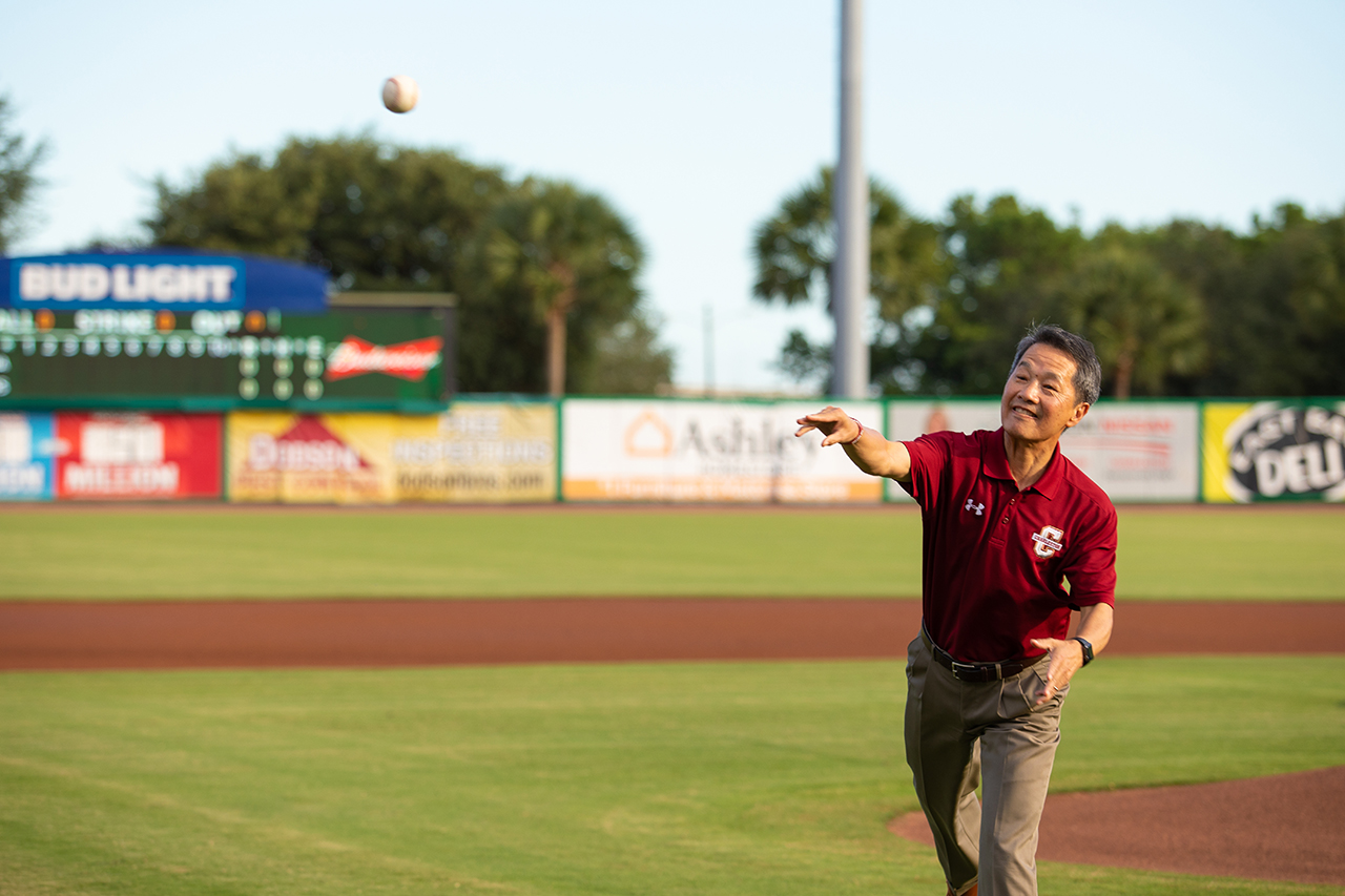 College of Charleston President Andrew T. Hsu throws the first pitch at a Charleston RiverDogs baseball game