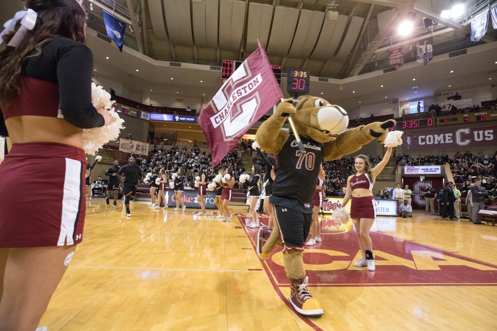 Clyde the Cougar waves a flag on the basketball court