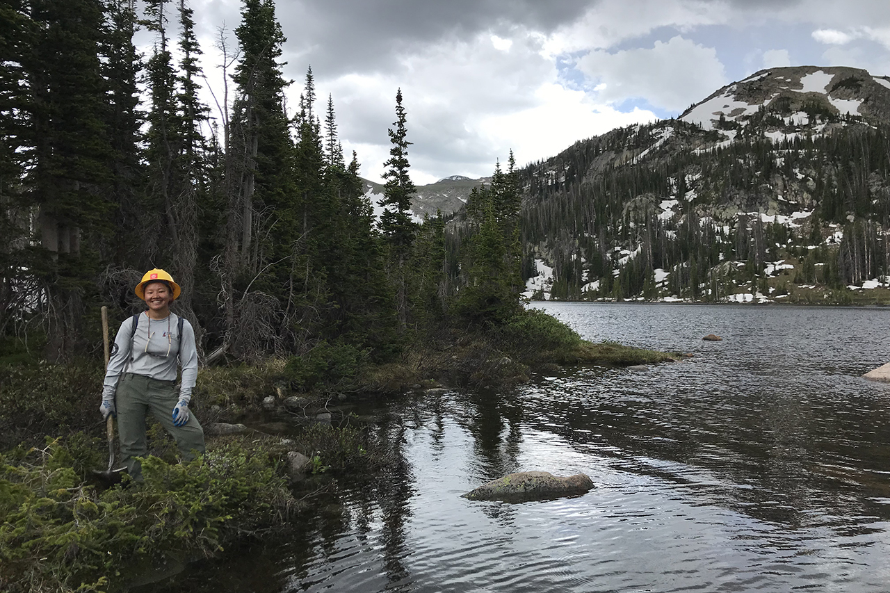 Sarah Sneath stands near a stream in the Rocky Mountains.