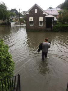A man carries his dog through a flooded street in a Charleston neighborhood
