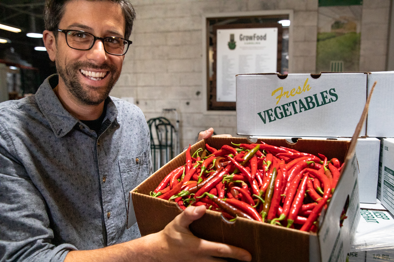 Grow Foods Carolina General Manager Anthony Mirisciotta holds up a box of red cayenne peppers that had been delivered that morning.