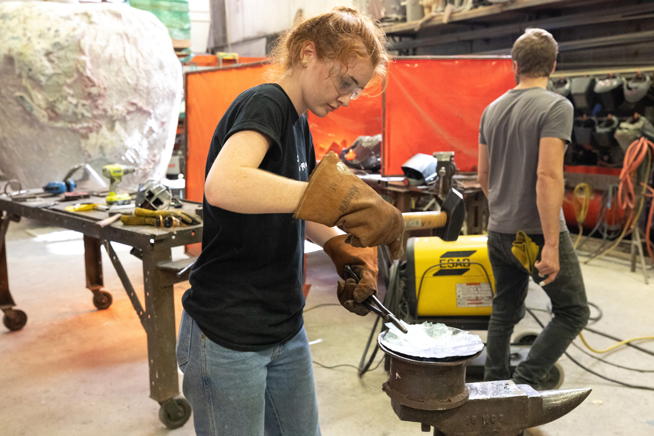 A student hammers on iron in the College of Charleston's blacksmithing class.