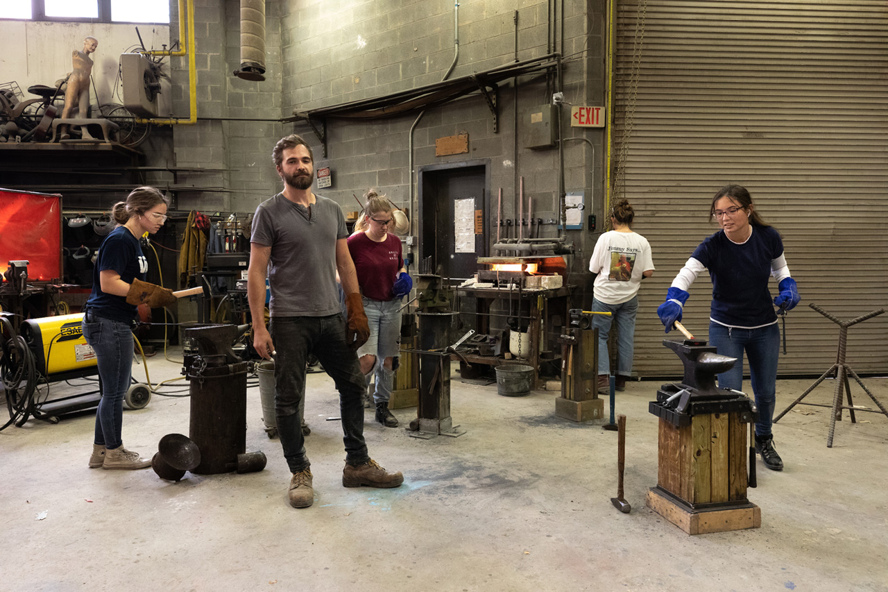 Carey Morton stands with students in his blacksmithing class