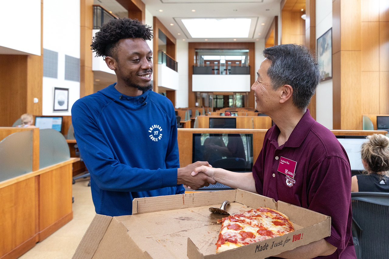 President Hsu gives out pizza in the library.