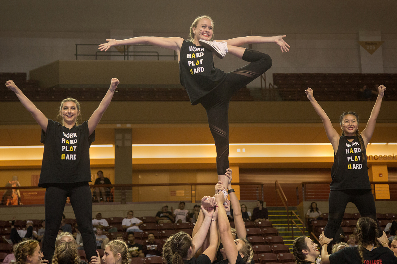 students do a cheer pose during a pep supper event