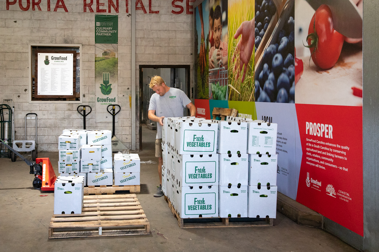 A worker at Grow Food Carolina unloads a crate of vegetables that were just unload from a truck.