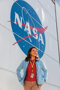 Dorlisa Hommel stands in front of the NASA logo