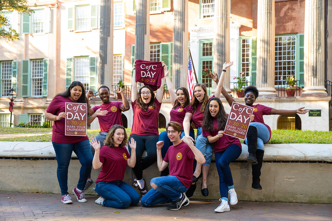 Students hold CofC Day signs and shirts