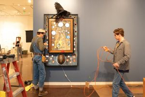 Butch Anthony installing his works at the Halsey.