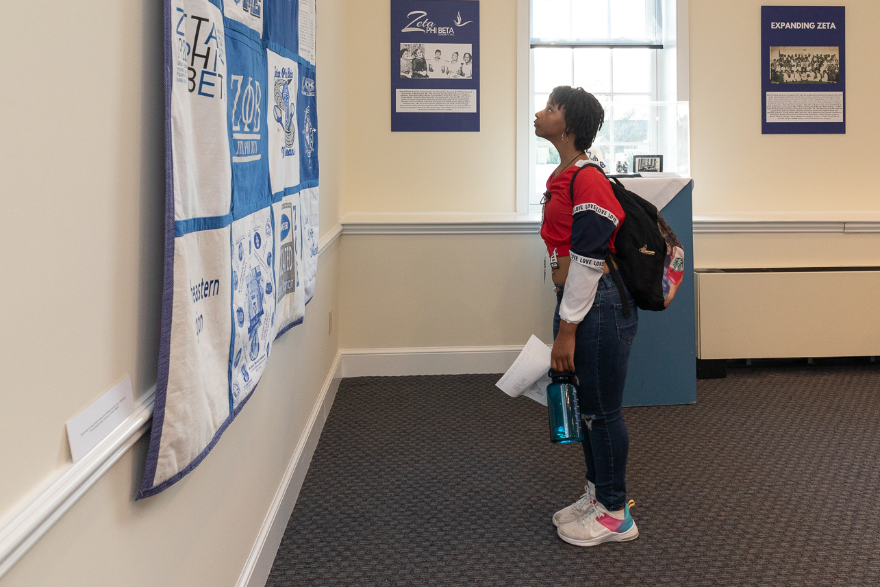 A visitor looks at a quilt in the Zeta Phi Beta Sorority exhibit room.