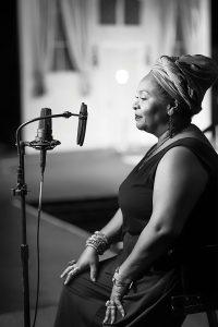 Joy Vandervort-Cobb sits in front of a recording microphone