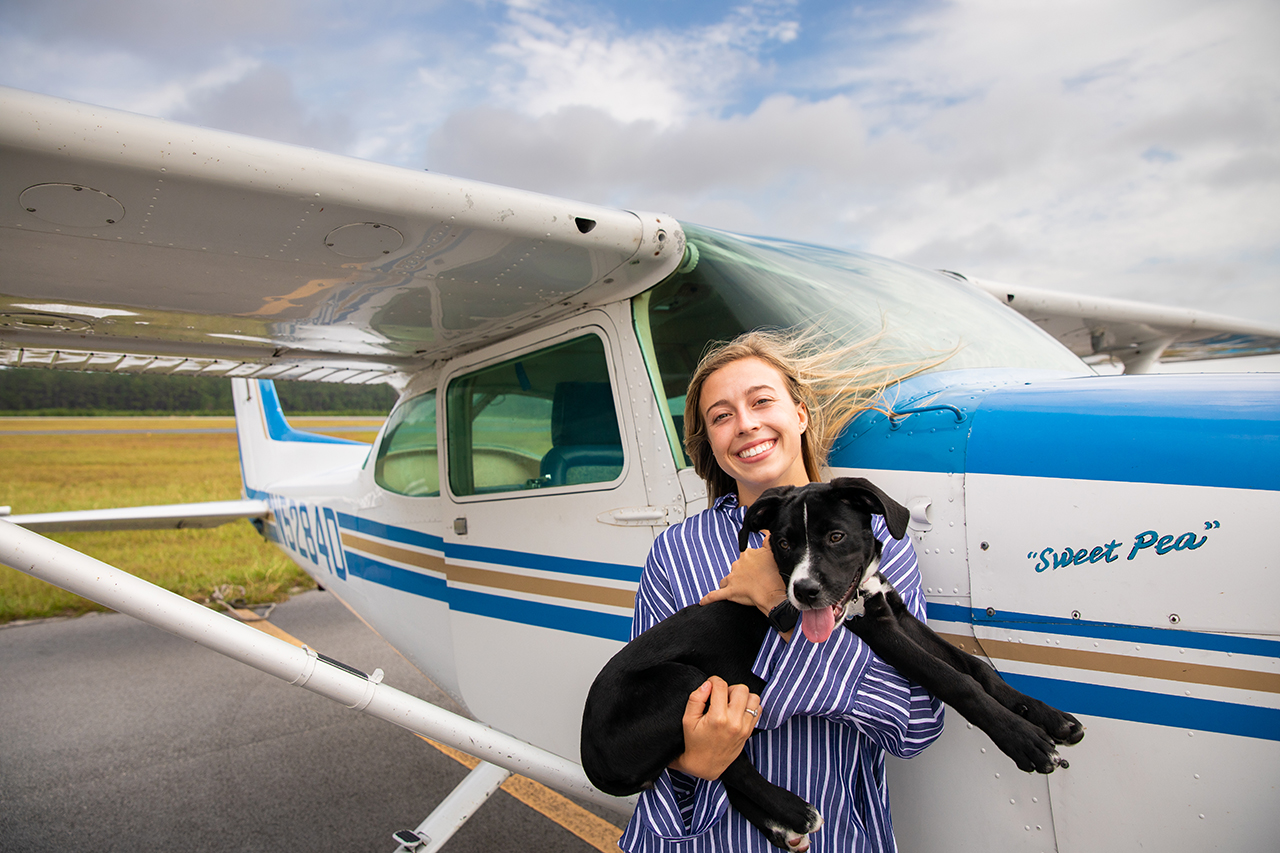 Samantha Bledsoe stands in front of a small airplane holding a dog