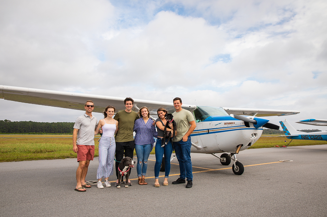 A group of people stands in front of a small airplane.