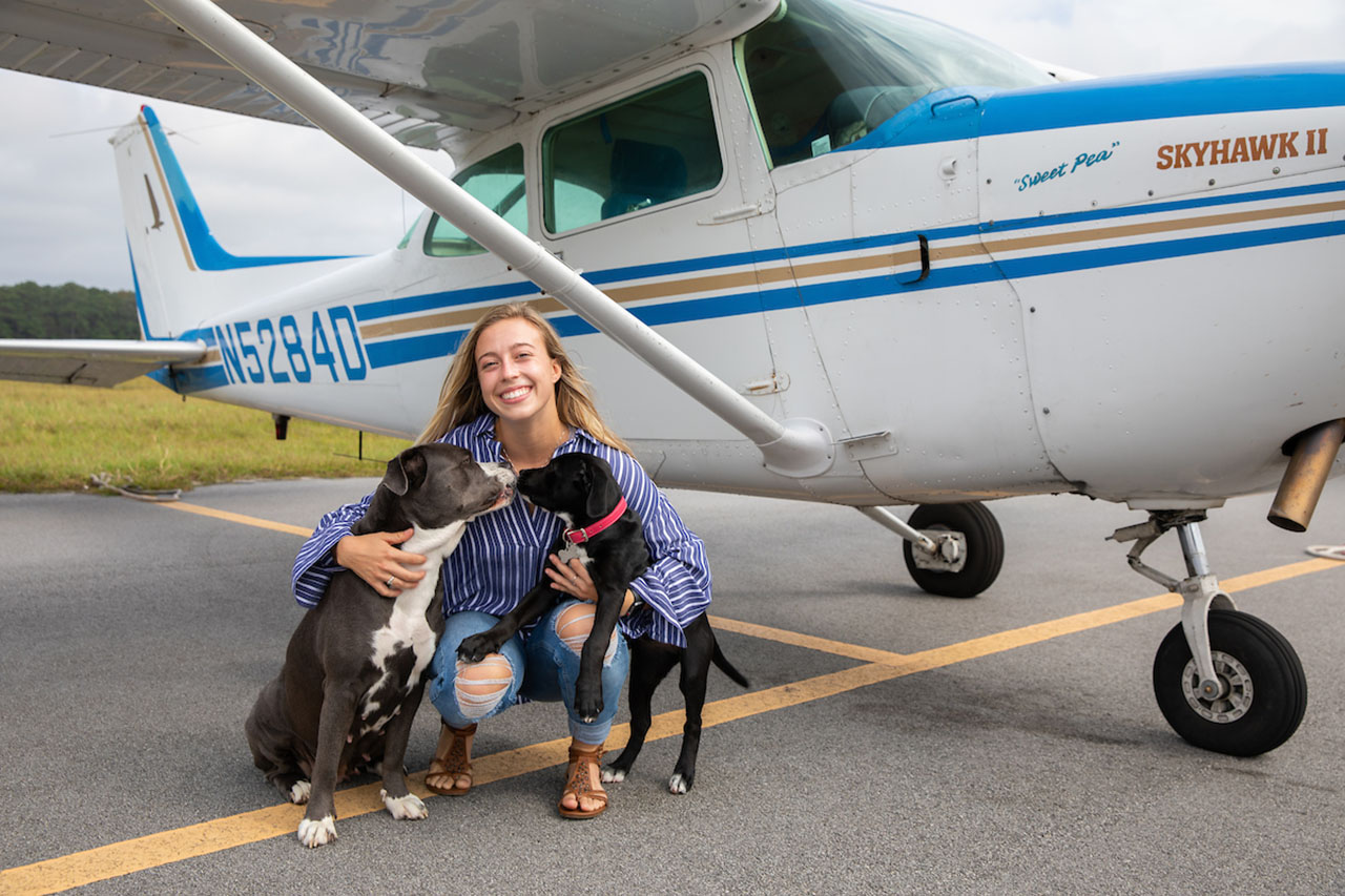 Samantha Bledsoe with dogs in front of a small airplane