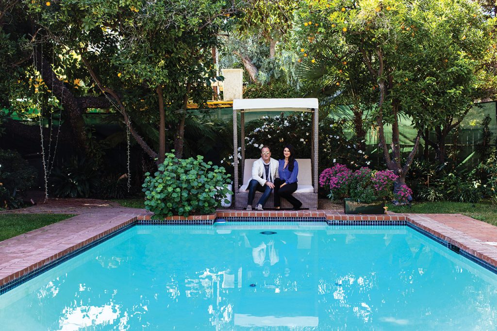 Will and Christy Ward sit on a swing by a pool