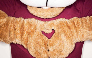 Clyde the cougar makes a heart shape with his hands