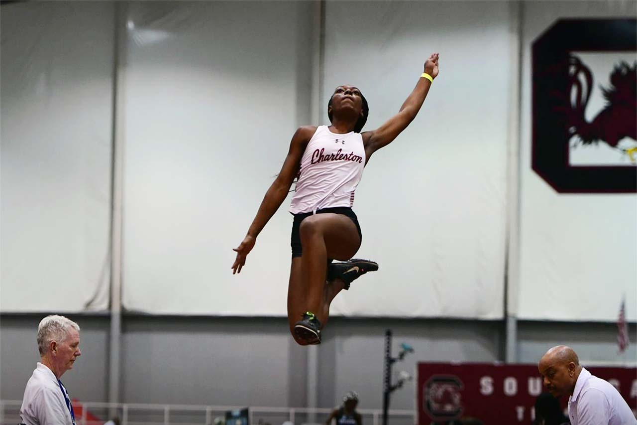 Womens track and field member competes at a meet