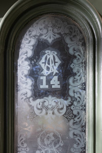 The initials of A.O. Jones appear in a stylized monogram etched in the glass above the number 14. Special thanks to Elizabeth Crimmins, who pointed out these initials in a Fall 2016 report she wrote for a class in the Department of Historic Preservation and Community Planning. Courtesy of the College of Charleston.
