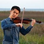 Tianyu Liu plays the violin with the marsh in the background