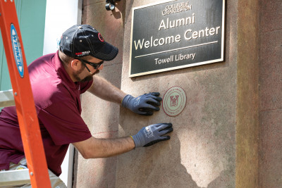 A worker installs a medallion on towell library
