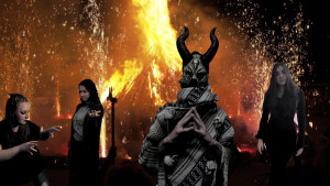 german theater students stand in front of a firey background and masked man with horns.