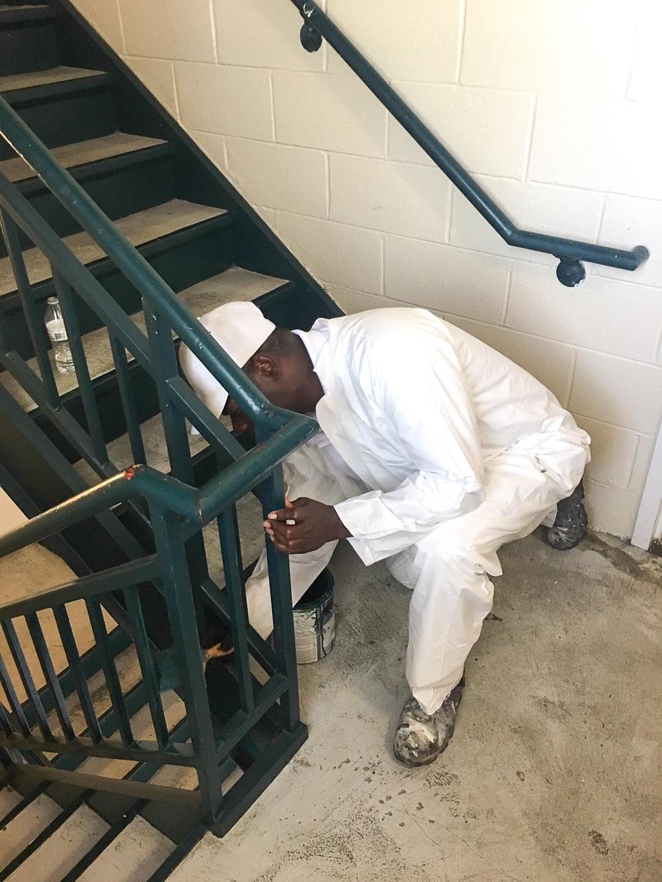 CofC Painter Remus Aiken paints the handrails at Warren Place during the 2020 COVID-19 pandemic.