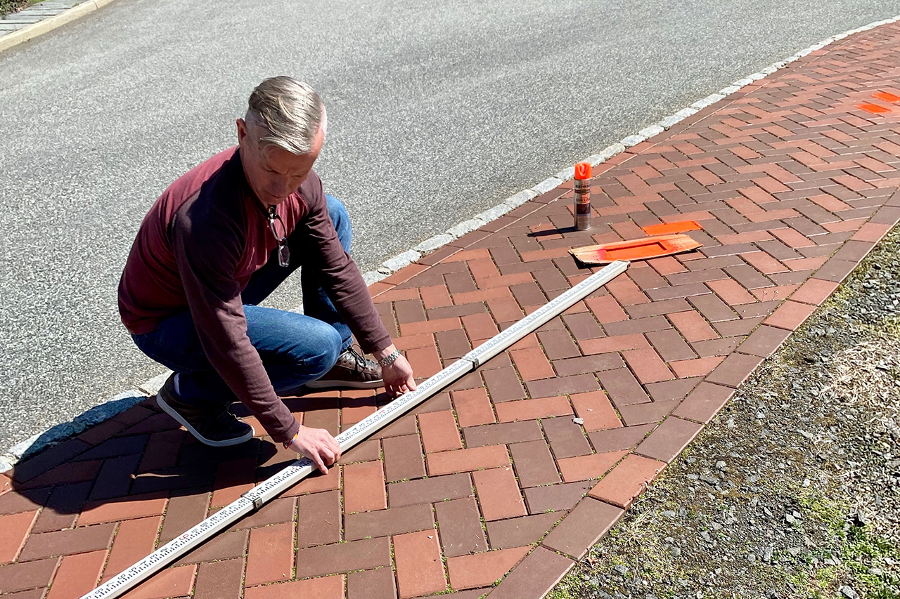 walter cain spray paints bricks orange to demonstrate the 6 feet recommendation for social distancing