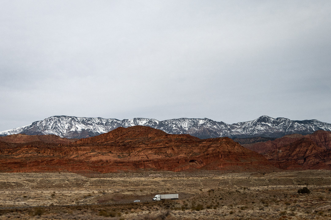A tractor trailer truck drives on I-95 with mountains in the background in Utah