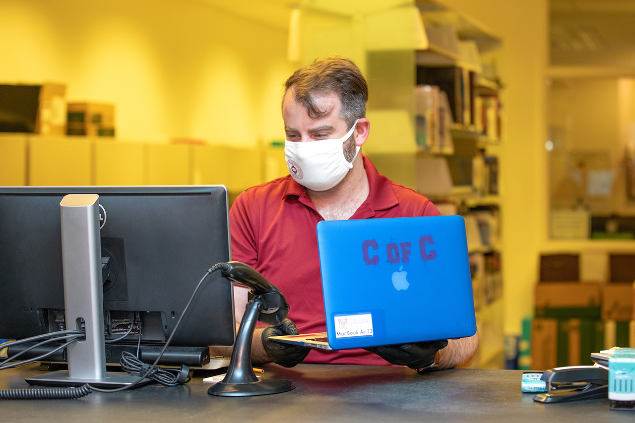 Will Breard checks out a laptop at the Addlestone library circulation desk for a student during the COVID-19 pandemic.