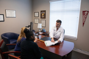 gary thomas meets with patients in his medical office