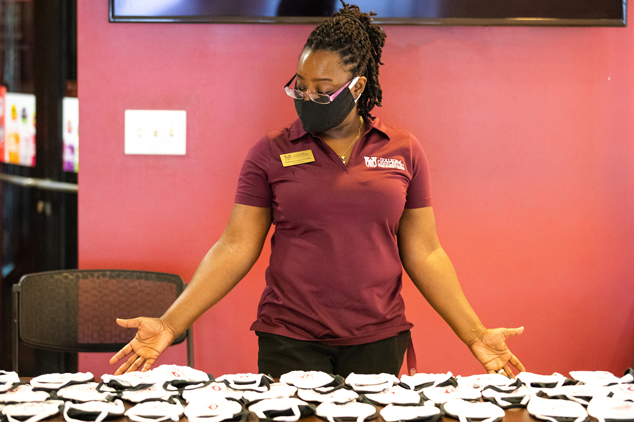 woman hands out face masks at stern student center