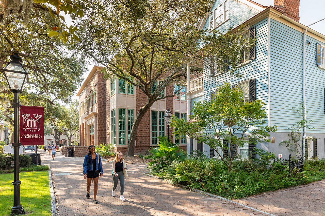 students walk past buildings on the college of charleston campus