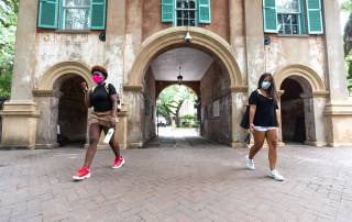 students wearing face masks walk on the college of charleston campus