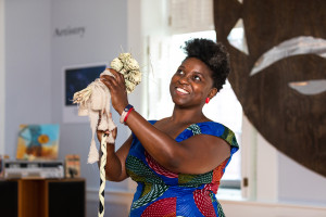 Tamara T. Butler the new Executive Director of the Avery Research Center for African American History and Culture at the College of Charleston and Associate Dean of College Libraries stands behind a microphone decorated with sweetgrass basket roses in the Second Floor Changing Room.