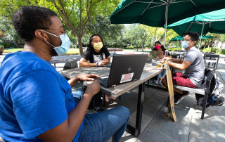 students wearing masks sit at tables outside addlestone library