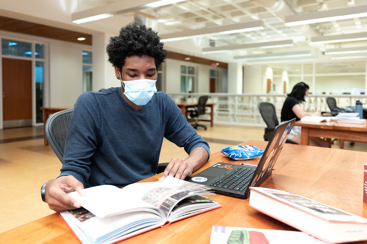 student using a laptop in the library while wearing a mask