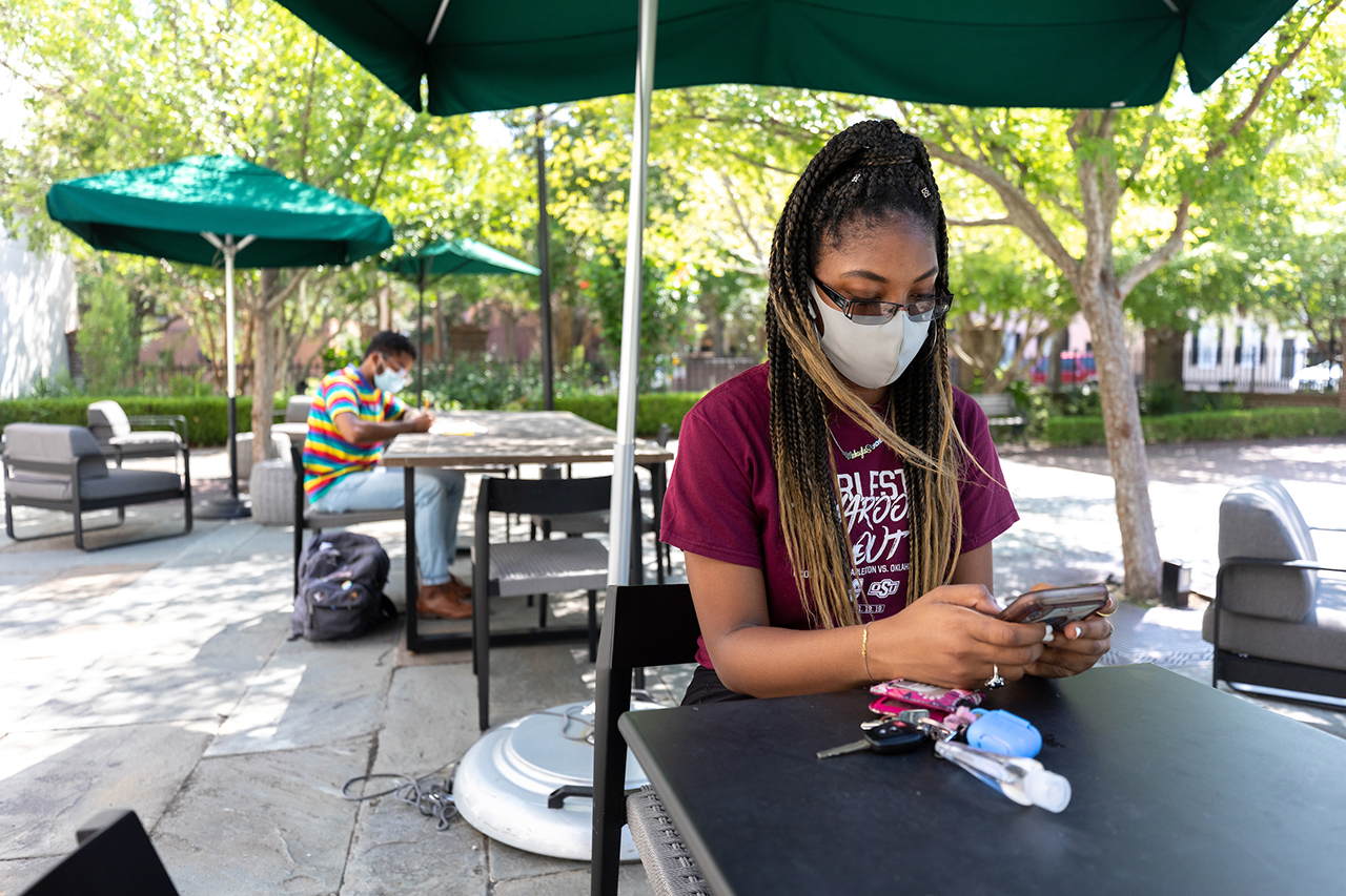 a student wearing a mask uses a cell phone