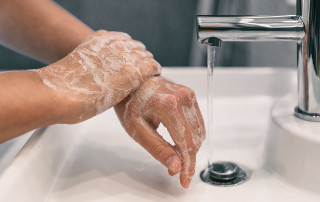 person washes their hands with soap and water