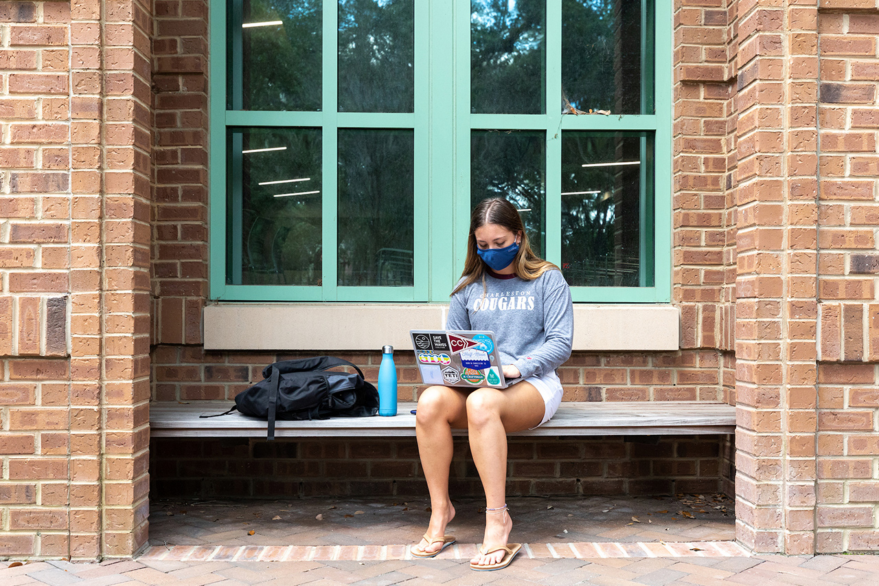 student wears a mask while working on a laptop